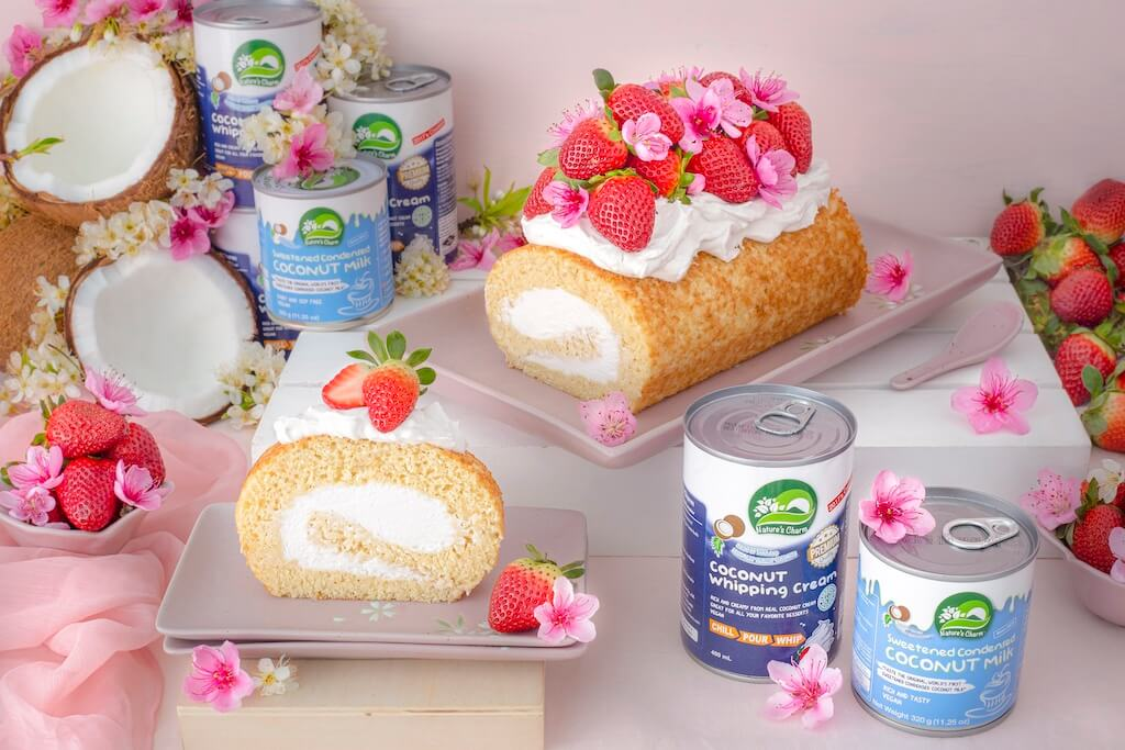 Vegan Coconut Swiss Roll decorated with fresh strawberries and flowers.